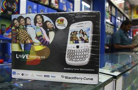 A salesman is seen behind the box of a blackberry handset at a shop in the southern Indian city of Kochi August 18, 2010. REUTERS/Sivaram V.