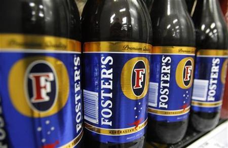 Bottles of Fosters beer are seen in a refrigerator at a liquor store in Melbourne February 16, 2010. REUTERS/Mick Tsikas
