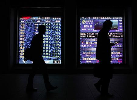 People are silhouetted against a board showing Japan's stock price index outside of a brokerage in Tokyo, August 20, 2010. REUTERS/Kim Kyung-Hoon