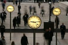 <p>People walk past clocks at reuters Plaza in London. REUTERS/Jon Jones/Handout</p>