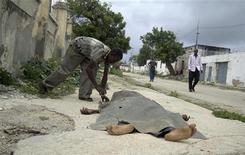 <p>Люди убирают с дороги тела людей, погибших в вооруженных конфликтах между исламистами и армией Сомали, 18 августа 2010 года. Вооруженные люди в армейской униформе ворвались в отель Huna Hotel в столице Сомали Могадишо, в котором находились представители властей, и убили по меньшей мере 31 человека во вторник, сообщило правительство. REUTERS/Stringer</p>