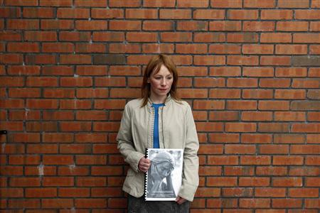 Tracy Deans, whose great uncle James McClelland died in the bombings of Claudy in 1972, stands for photographers with a copy of the report by the Police Ombudsman, Claudy, Northern Ireland, August 24, 2010. REUTERS/Cathal McNaughton