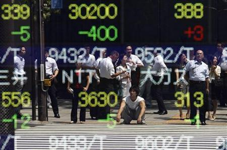 People are reflected in a board outside a brokerage in Tokyo, August 24, 2010. REUTERS/Toru Hanai