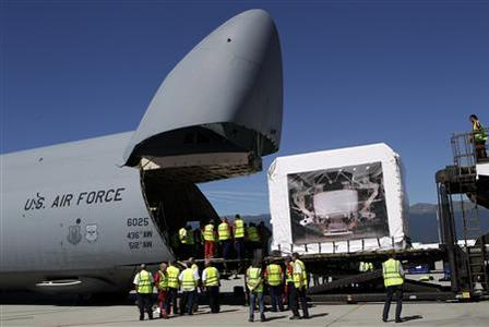 Staff talk next the Alpha Magnetic Spectrometer (AMS) detector after a failed attempt to load it into a U.S. Air Force Galaxy aircraft during last preparations at Cointrin Airport in Geneva, August 25, 2010. REUTERS/Denis Balibouse