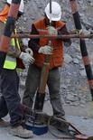 """<p>Unos trabajadores descienden un tubo con elementos de ayuda para unos 33 mineros atrapados en la mina San José en Copiapó, Chile. ago 25 2010. a odisea que enfrentan los operarios de una mina en Chile para sobrevivir en """"las entrañas del infierno"""" durante meses supera la ficción, pero para el autor Hernán Rivera Letelier aún es impensable escribir sobre ella. REUTERS/Ivan Alvarado</p>"""