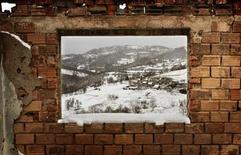 <p>A village is seen through the window of the destroyed house of the only Muslim returnee in the village of Vinca in the Serb part of Bosnia November 20, 2005. REUTERS/Damir Sagolj</p>