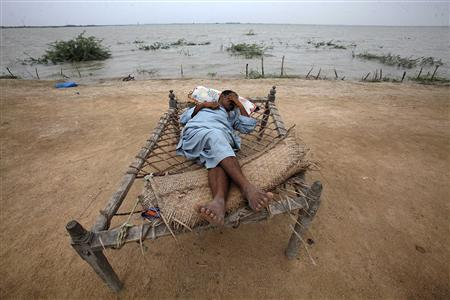 A flood victim villager rests on a handmade rope bed while taking refuge on an embankment with his family in Sujawal, about 150 kilometres (93 miles) from Karachi in Pakistan's Sindh province August 29, 2010. REUTERS/Akhtar Soomro
