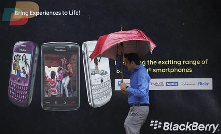 A man tries to hold on to his umbrella as he walks past a Blackberry advertisement billboard in Mumbai August 30, 2010. Officials meet on Monday to decide whether to ban some of Research In Motion's BlackBerry services, a day before the deadline runs out for the firm to give security agencies access to its secure data. REUTERS/Danish Siddiqui