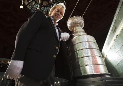 ''Keeper of the Cup'' Phil Pritchard, poses beside the National Hockey League's (NHL) Stanley Cup at the Hockey Hall of Fame in Toronto August 17, 2010. REUTERS/Mark Blinch