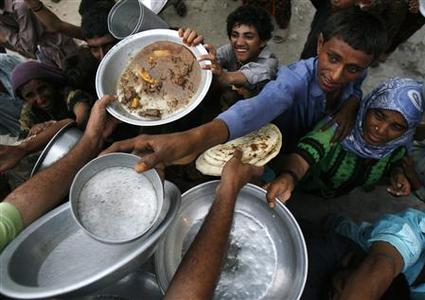 Flood victims receive free food, distributed by a charity organisation in a relief camp in Sukkur, Pakistan's Sindh province September 1, 2010. REUTERS/Athar Hussain