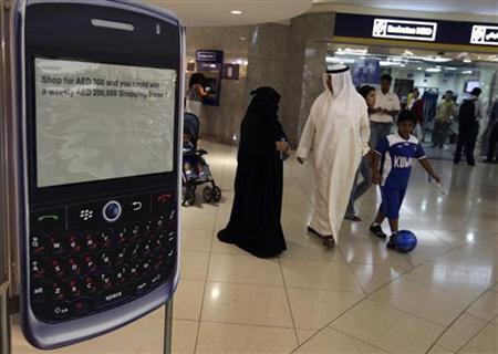 A family walks past a display of a BlackBerry smart phone at a shopping mall in Dubai August 1, 2010. REUTERS/Mosab Omar