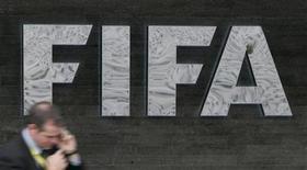 <p>Человек проходит мимо вывески ФИФА у штаб-квартиры организации в Цюрихе 29 октября 2007 года. Европейские футбольные клубы недовольны действиями ФИФА в отношении календаря национальных команд и постоянными травмами, которые игроки получают в играх за свои сборные, сообщил глава Ассоциации европейских клубов (ECA) Карл- Хайнц Румменигге. REUTERS/Michael Buholzer</p>