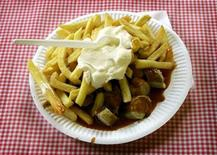 <p>A typical German fast food dish of 'Currywurst with chips', which is a sausage with curry powder and ketchup served with fries, is pictured at a takeaway in Dortmund May 22, 2006. REUTERS/Ina Fassbender</p>