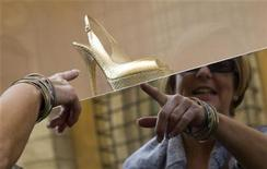<p>A woman looks at a Jimmy Choo open-toed slingback shoe displayed in a shop window on Via Condotti in central Rome October 7, 2008. REUTERS/Tony Gentile</p>