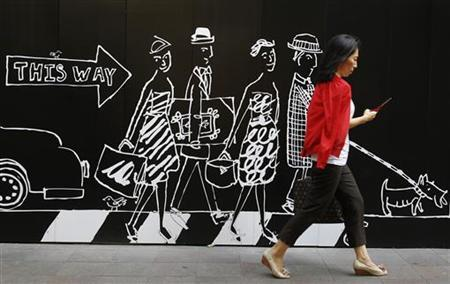 A woman walks in front of an advertisement for a clothing store in Tokyo September 10, 2010. REUTERS/Yuriko Nakao