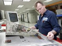 <p>Detroit Newspapers journeyman pressman Frank Brabenec proof reads for print errors a first edition of The Detroit News newspaper at the newspapers printing plant in Sterling Heights, Michigan December 16, 2008. REUTERS/Rebecca Cook</p>