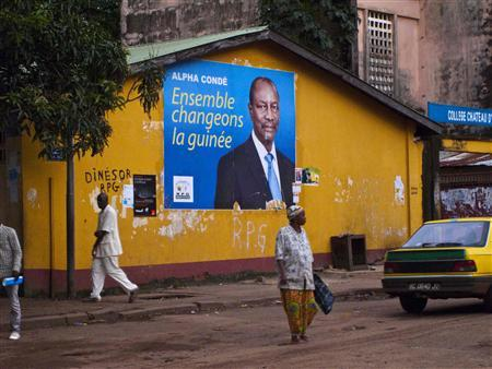 Pedestrians walk past a poster for Guinea presidential candidate Alpha Conde in Conakry, September 13, 2010. REUTERS/Joseph Penney
