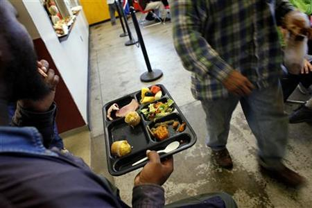 A homeless man holds his plate of food at the Urban Ministry soup kitchen in Charlotte, North Carolina November 15, 2009. REUTERS/Carlos Barria