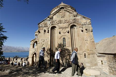 People walk around the Church of the Holy Cross, an Armenian church on Akdamar Island in Lake Van, near the eastern Turkish city of Van September 19, 2010. REUTERS/Umit Bektas