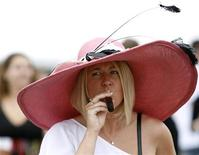 <p>Женщина курит сигару перед началом конных заездов в Балтиморе, 16 мая 2009 года. 21 сентября 2004 года крупнейшие табачные компании вступили в судебную тяжбу с правительством США, которое предъявило им иск на $280 миллиардов, обвинив их в намеренном обмане общественности с 1950-х годов в отношении вреда для здоровья от курения. REUTERS/Jose Luis Magana</p>