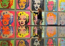 <p>Сотрудница аукционнного дома Bonhams в Лондоне поправляет картину Энди Уорхола, 2 августа 2010 года. Более 200 работ, включая картины Энди Уорхола и Жан-Мишеля Баскии из личной коллекции Денниса Хоппера, будут выставлены на двух аукционах Christie's. REUTERS/Toby Melville</p>