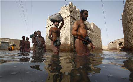 Villagers displaced by flooding wade through floodwaters as they return to their flooded village of Bello Patan, in Pakistan's Sindh province, September 21, 2010. REUTERS/Akhtar Soomro