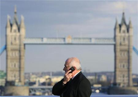 A man talks on a mobile telephone in front of Tower Bridge whilst walking across London Bridge in London March 1, 2010. REUTERS/Luke MacGregor