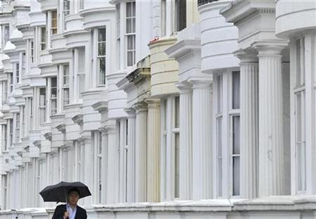 A man walks past a terrace of houses in London August 10, 2010. REUTERS/Toby Melville