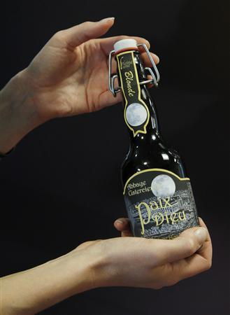 A woman holds up a bottle of Paix-Dieu beer in Brussels September 24, 2010. REUTERS/Thierry Roge