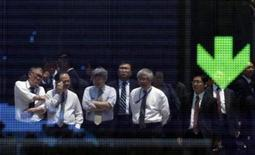 <p>Businessmen are reflected in an electronic board displaying a downward arrow for the Nasdaq index outside a brokerage in Tokyo May 25, 2010. REUTERS/Yuriko Nakao</p>