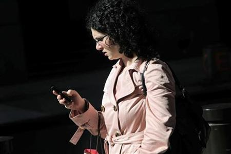A woman uses a smartphone to perform various tasks in New York in this September 25, 2009 file photo. REUTERS/Natalie Behring