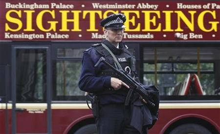 An armed police officer waits to cross the road opposite Downing Street as a tour bus passes behind him, in Westminster, central London, September 29, 2010. REUTERS/Andrew Winning