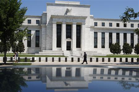 The U.S. Federal Reserve is reflected in a car as a security officer patrols the front of the building in Washington, in this file imager from June 24, 2009. REUTERS/Jim Young