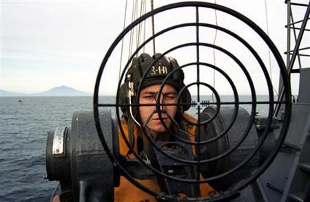 A Russian border guard takes aim on board a patrol boat off the island of Tanfilyeva, part of the Kurile Islands, referred to as the Northern Territories in Japanese in this August 2000 file picture. REUTERS/Yuri Maltsev