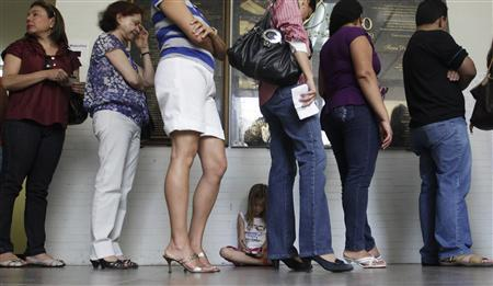 A girl sits as people wait in line to vote at a polling station during Brazil's general elections in Brasilia October 3, 2010. REUTERS/Ricardo Moraes