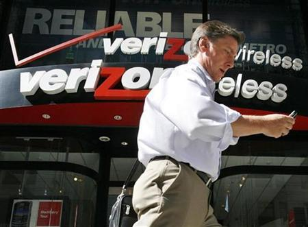 A man looks at his phone as he walks past a Verizon wireless store in New York, July 30, 2009. REUTERS/Brendan McDermid
