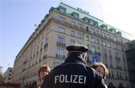A policeman talks to tourists as he patrols in front of the Hotel Adlon at Pariser Platz in Berlin, October 4, 2010. REUTERS/Fabrizio Bensch