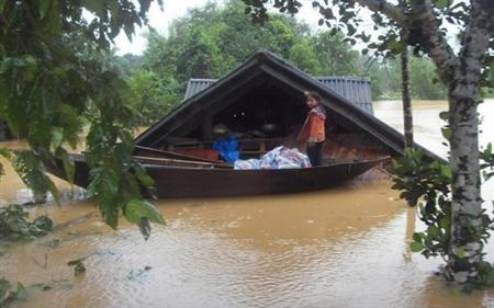 A girl stands on a boat near her submerged house in a flooded area of Vietnam's central Ha Tinh province October 5, 2010. REUTERS/VNA/Cong Tuong
