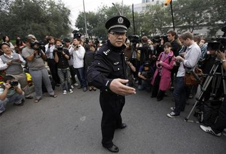 A policeman gestures to reporters at the entrance of a residential compound where Liu Xia lives in Beijing October 8, 2010. REUTERS/Petar Kujundzic