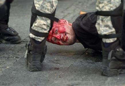 A wounded protester is detained by police during riots in Belgrade October 10, 2010. REUTERS/Milos Peric