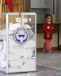 <p>Мальчик проходит мимо избирательной урны в деревне Байтык, пригород Бишкека 10 октября 2010 года. В Киргизии 10 октября состоятся досрочные парламентские выборы, в результате которых страна станет первой в Центральной Азии парламентской республикой. REUTERS/Shamil Zhumatov</p>