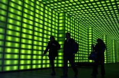 <p>Office workers walk through a green lit foyer of an office building in Melbourne May 5, 2009. REUTERS/Mick Tsikas</p>