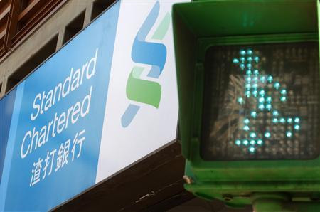 A Standard Chartered logo is seen beside a traffic light at a junction in Taipei October 13, 2010. REUTERS/Nicky Loh