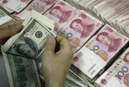 An employee counts U.S. dollar banknotes at a branch of the Industrial and Commercial Bank of China in Huaibei, Anhui province in this May 25, 2010 file photo. REUTERS/Stringer