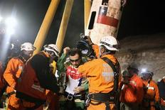 "<p>Trapped miner Raul Bustos (C) emerges from the ""Phoenix"" rescue capsule after reaching the surface to become the 30th to be rescued from the San Jose mine in Copiapo October 13, 2010. REUTERS/Hugo Infante/Government of Chile/Handout</p>"