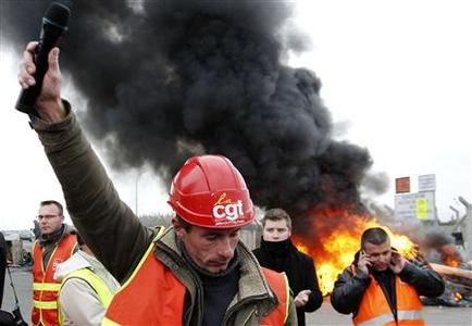 Christophe Hiou, worker of French oil giant Total and CGT labour union representative, delivers a speech as workers of French oil giant Total and the SFDM Society, and SNCF railway workers block the entrance of the deposit of the society SFDM near the oil refinery of Donges, near Nantes, October 15, 2010. REUTERS/Stephane Mahe