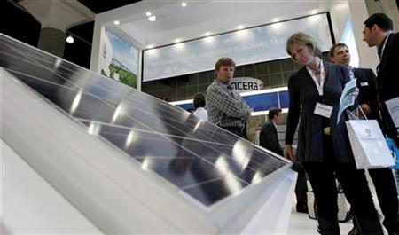 Attendees look over a solar panel display at the Q-Cells booth at the Solar Power International 10 exhibition in Los Angeles October 12, 2010. REUTERS/Fred Prouser