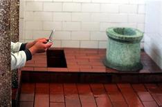 <p>Мужчина пользуется телефоном в общественной уборной, Пекин 18 ноября 2004 года.Усилия спасателей понадобились, чтобы помочь попавшему в щекотливую ситуацию китайцу, который попытался достать упавший в сливное отверстие унитаза телефон, сообщил государственный телеканал CCTV во вторник. REUTERS/Claro Cortes</p>