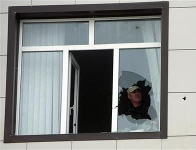 A man looks at a broken window in the parliament building in Grozny October 19, 2010. REUTERS/Kazbek Basayev