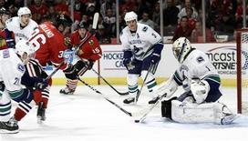 """<p>Игроки """"Чикаго"""" и """"Ванкувера"""" борются за шайбу, Чикаго 20 октября 2010 года. Действующему обладателю Кубка Стэнли """"Чикаго"""" понадобилась серия буллитов, чтобы обыграть дома """"Ванкувер"""". REUTERS/John Gress</p>"""